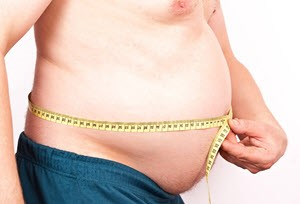 Obese man measuring stomach